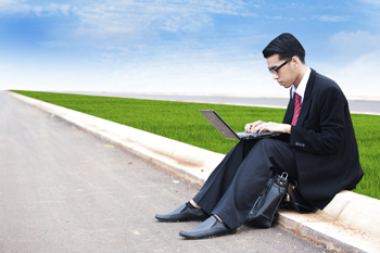 Asian businessman working on laptop outdoor